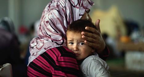 En syrisk kvinna tröstar sitt barn. De har flytt från kriget i Syrien. Fler än två miljoner människor har flytt från Syrien.